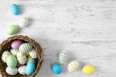 Colorful easter eggs in wicker on white rustic background.