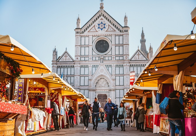 Florence, Italy - December 11, 2015: View of Christmas market at the Piazza Santa Croce in Florence during the christian period with the christiam market. The place is full of people doing shopping on the city.